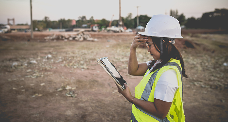 Female construction worker onsite looking at a tablet