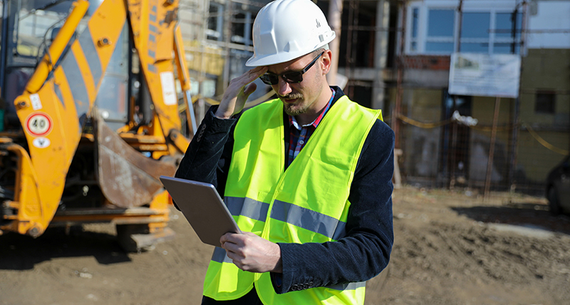 Construction worker onsite looking at tablet